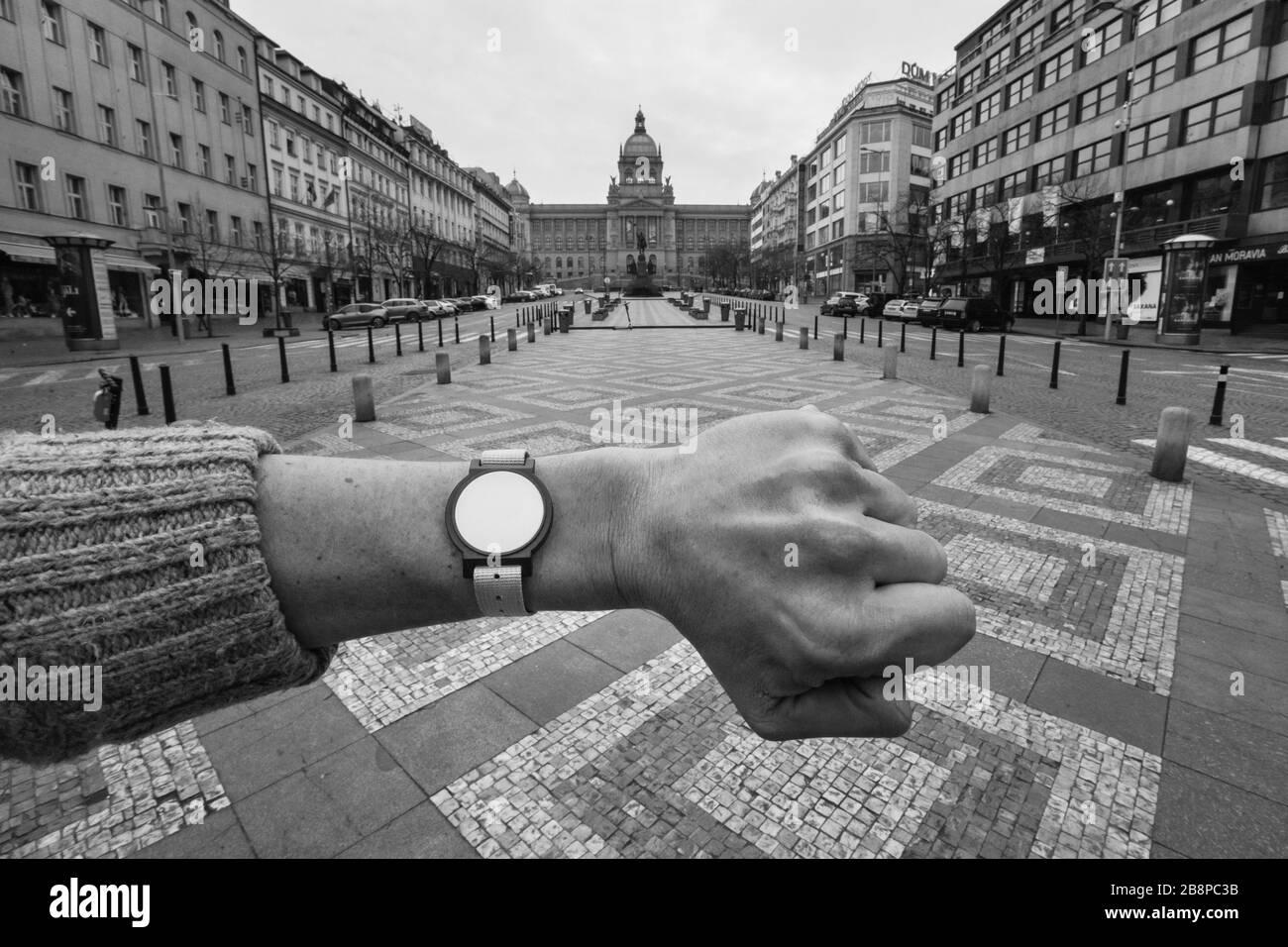 Casi desolada Plaza Wenceslas (Václavské náměstí) en Praga, República Checa, fotografiada a las 1.27 horas durante la cuarentena pandémica del coronavirus COVID-19 (bloqueo) el 19 de marzo de 2020. La fotografía es un homenaje a la famosa fotografía del fotógrafo checoslovaco Josef Koudelka, representada en el mismo lugar durante la invasión soviética a Checoslovaquia en agosto de 1968. El reloj sin manos a la izquierda del fotógrafo es en realidad un chip de entrada al Aquacentrum Šutka que es inútil durante la cuarentena porque todas las piscinas también están cerradas indefinidamente debido al brote del virus de la corona. Foto de stock