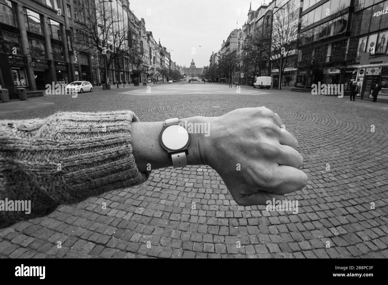 Casi desolada Plaza Wenceslas (Václavské náměstí) en Praga, República Checa, fotografiada a las 1.17 horas durante la cuarentena pandémica del coronavirus COVID-19 (bloqueo) el 19 de marzo de 2020. La fotografía es un homenaje a la famosa fotografía del fotógrafo checoslovaco Josef Koudelka, representada en el mismo lugar durante la invasión soviética a Checoslovaquia en agosto de 1968. El reloj sin manos a la izquierda del fotógrafo es en realidad un chip de entrada al Aquacentrum Šutka que es inútil durante la cuarentena porque todas las piscinas también están cerradas indefinidamente debido al brote del virus de la corona. Foto de stock
