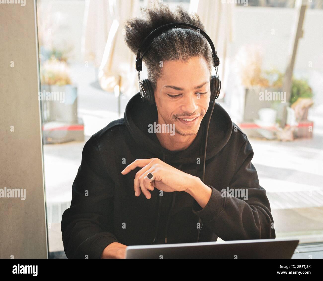 El hombre afro americano creativo, con pelo extraño, está estudiando y creando nuevo contenido para su blog personal, latinoamericano trabajando en proyecto web, lifest Foto de stock