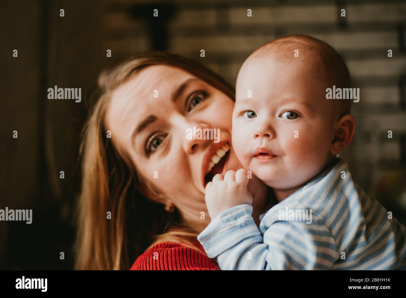 Una mamá sostiene a un bebé en sus brazos. La madre se jala a su hijo. Una mujer joven se divierte y se regocija con el niño. Una niña se embraga a un infant.Close para arriba. Foto de stock