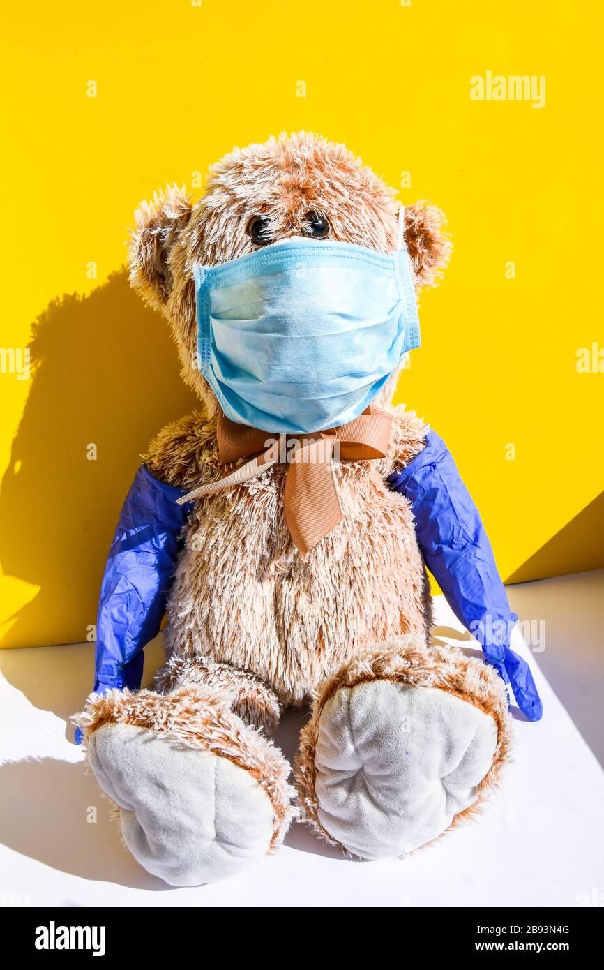 Coronavirus covid-19 y concepto de protección contra la contaminación. Muñeca de oso de peluche con máscara y guantes protectores sobre fondo amarillo, espacio de copia Foto de stock