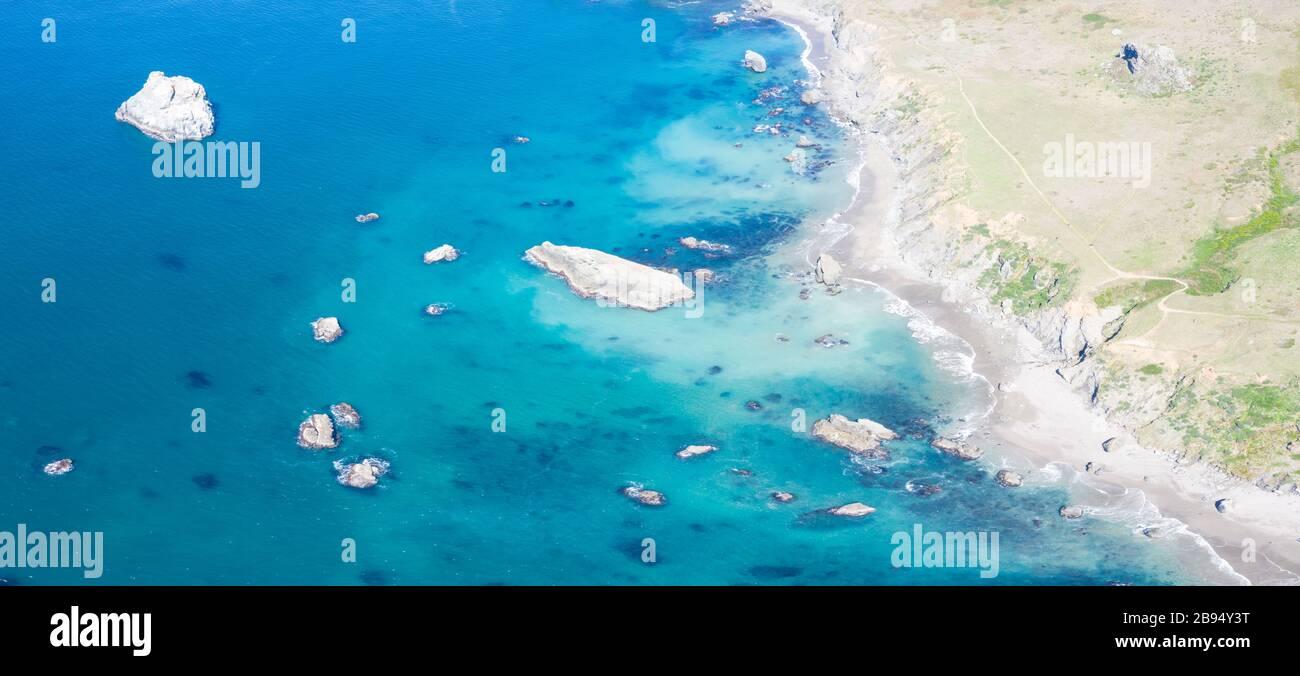 El colorido y casi pacífico Océano Pacífico se lava contra la rocosa costa del norte de California en un hermoso día. Foto de stock