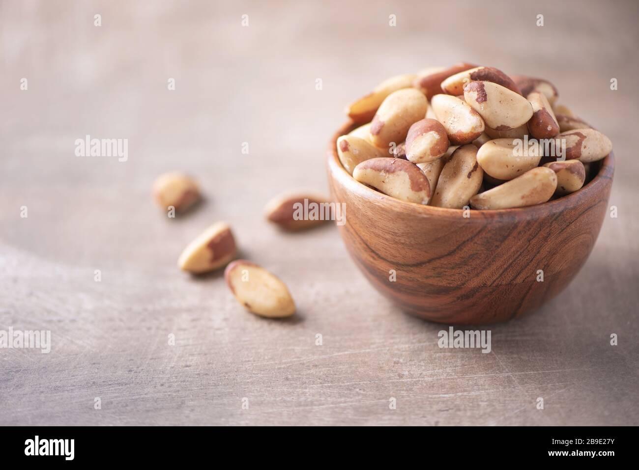 Nueces de Brasil en cuenco de madera sobre fondo texturizado de madera. Espacio de copia. Superfood, vegan, comida vegetariana concepto. Macro de la textura de la nuez de brasil, selectiva Foto de stock