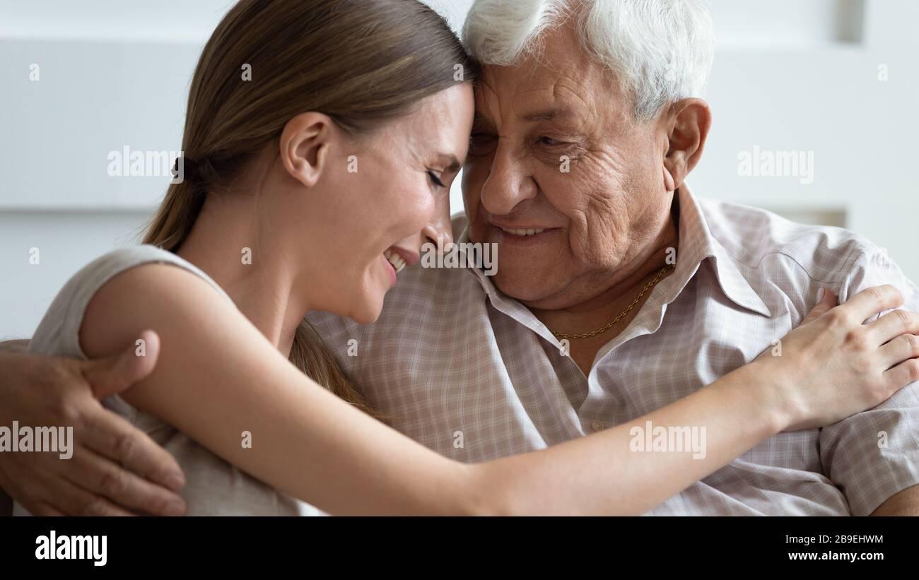 Amando a la hija adulta y al padre mayor tocando frentes, amando Foto de stock