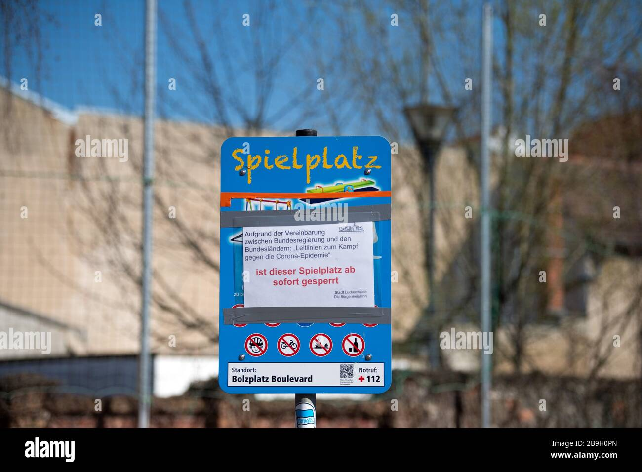 Luckenwalde, Alemania. 24 de marzo de 2020. En un cartel junto a una cancha de voleibol, hay un aviso que indica que el patio de juegos está cerrado debido a la pandemia de Corona. La ciudad quiere imponer la prohibición a las multitudes en parques y áreas públicas, marcándolas con cinta de barrera. Crédito: Soeren Stache/dpa-Zentralbild/dpa/Alamy Live News Foto de stock