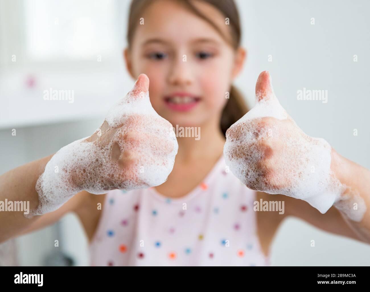 Niña que se lava las manos con agua y jabón en el baño. Niño mostrando un aprobado. Higiene de las manos y prevención de infecciones por virus. Foto de stock