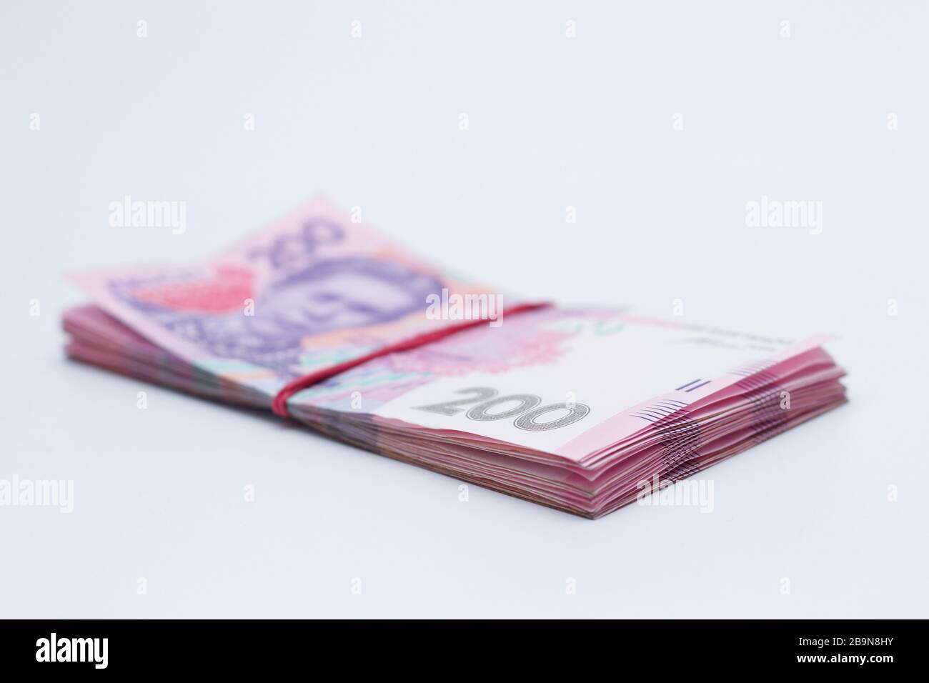 Muchos billetes nuevos en denominaciones de 200 hryvnias ucranianas vendados con una banda elástica aislada en un fondo blanco con sombra. Europa m Foto de stock