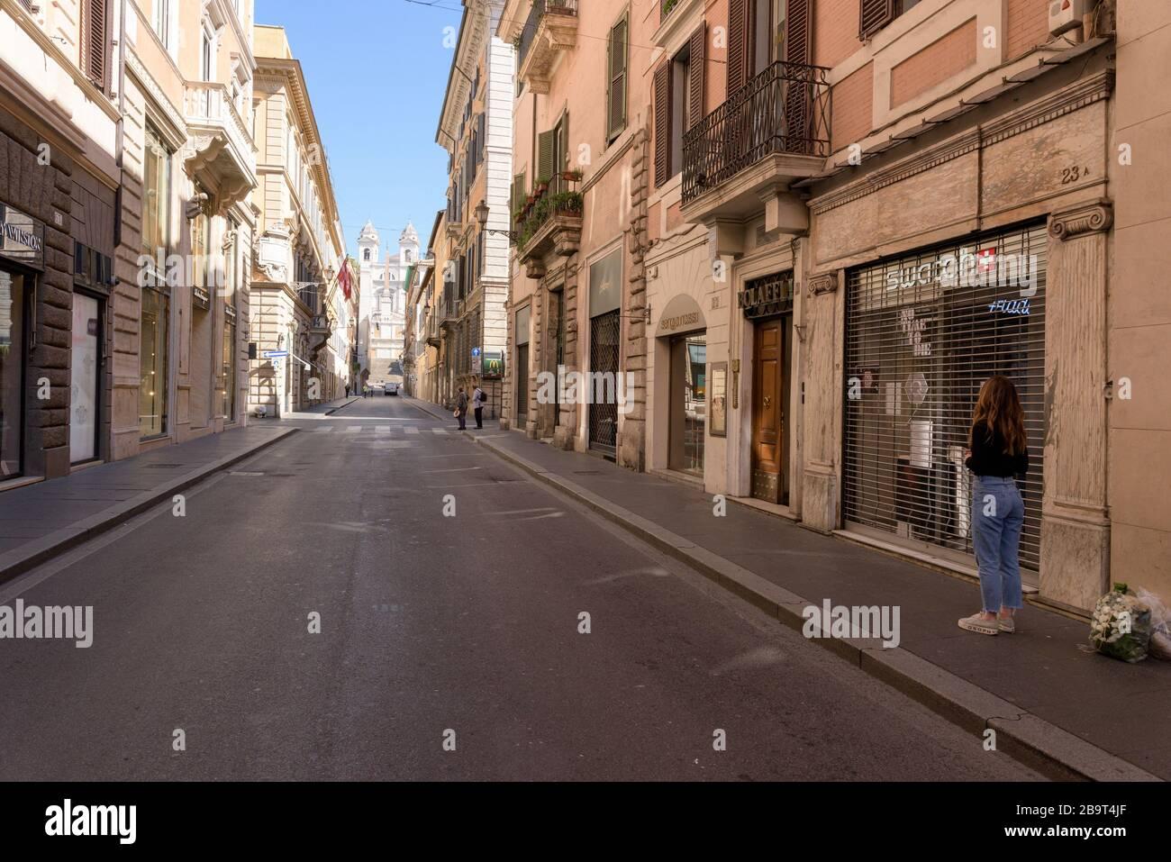 ROMA, ITALIA - 12 de marzo de 2020: Una mujer se encuentra frente a las tiendas cerradas de Via dei Condotti, junto a la Plaza de España, Roma, Italia. Uno debe justificar el Foto de stock