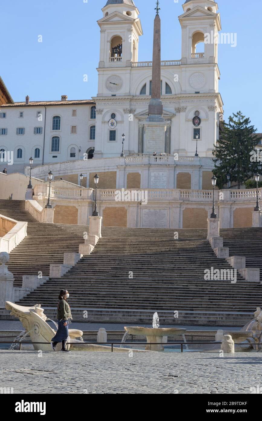 ROMA, ITALIA - 10 de marzo de 2020: Una mujer turística que lleva una máscara de cara camina frente a los pasos españoles en Roma, Italia. Hoy, el gobierno italiano Foto de stock