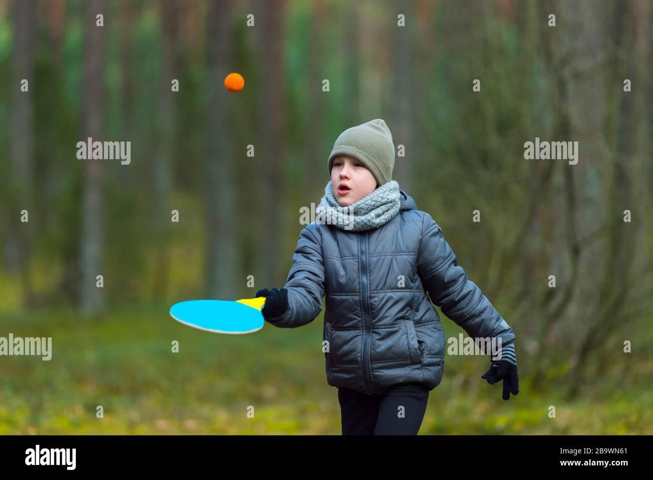 Un niño pequeño con una máscara debido al virus de la corona juega al tenis en el parque. Cuarentena de coronavirus Foto de stock