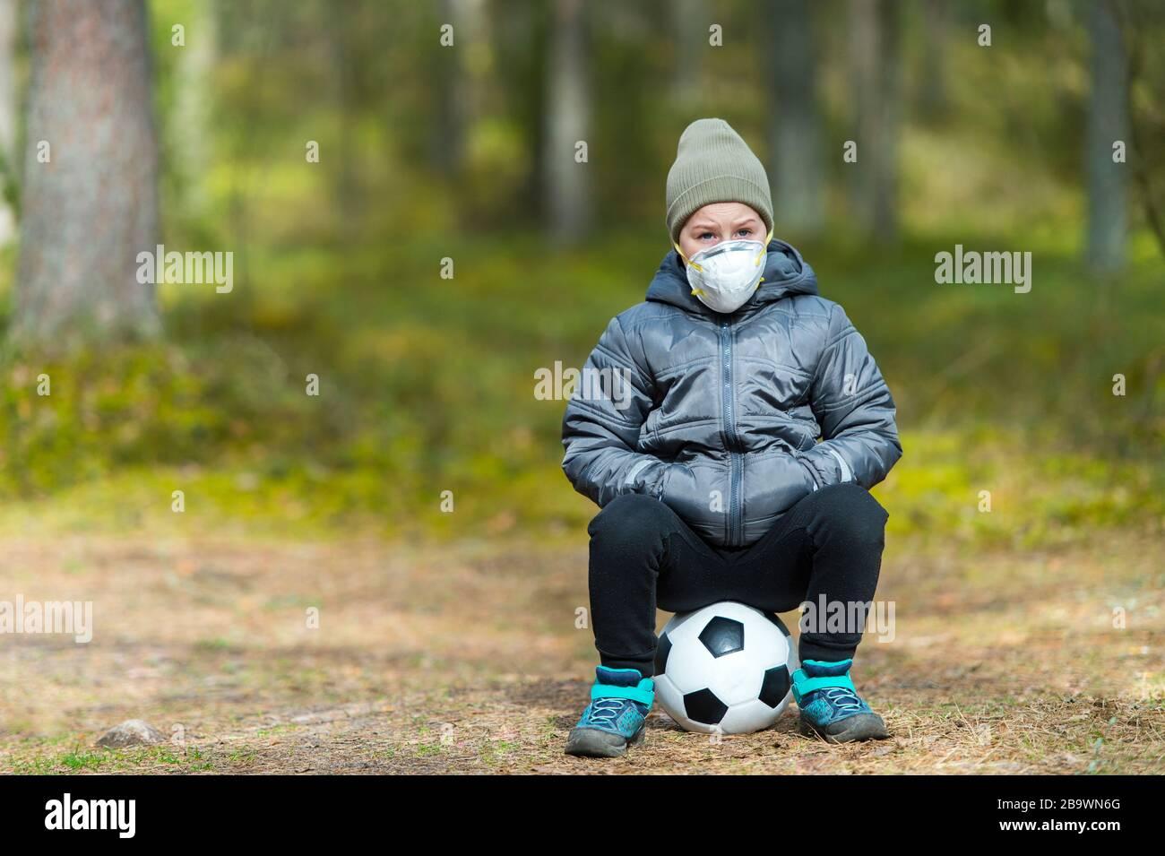 Niño pequeño con una máscara y una pelota de fútbol en el parque. Cuarentena del virus de la corona Foto de stock