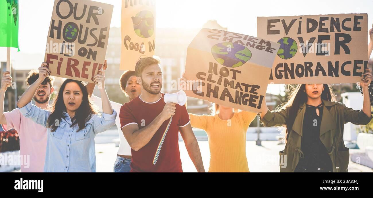 Grupo de manifestantes en la carretera, jóvenes de diferentes culturas y razas luchan por el cambio climático - concepto de calentamiento global y medio ambiente - Focus Foto de stock