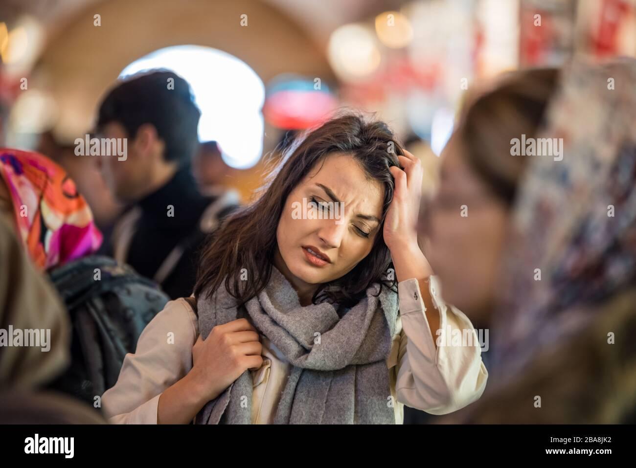 Una mujer hermosa con ropa moderna de moda sufre problemas de migraña o dolor de cabeza mientras se encuentra de pie multitud de personas en la carretera. Foto de stock