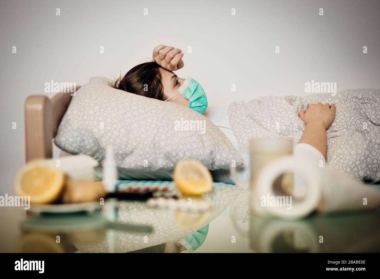 Mujer enferma con mascarilla en cama de cuarentena autoaislamiento.Coronavirus Covid-19 paciente con neumonía enfermedad síntomas.Prevención y tratamiento de la salud Foto de stock