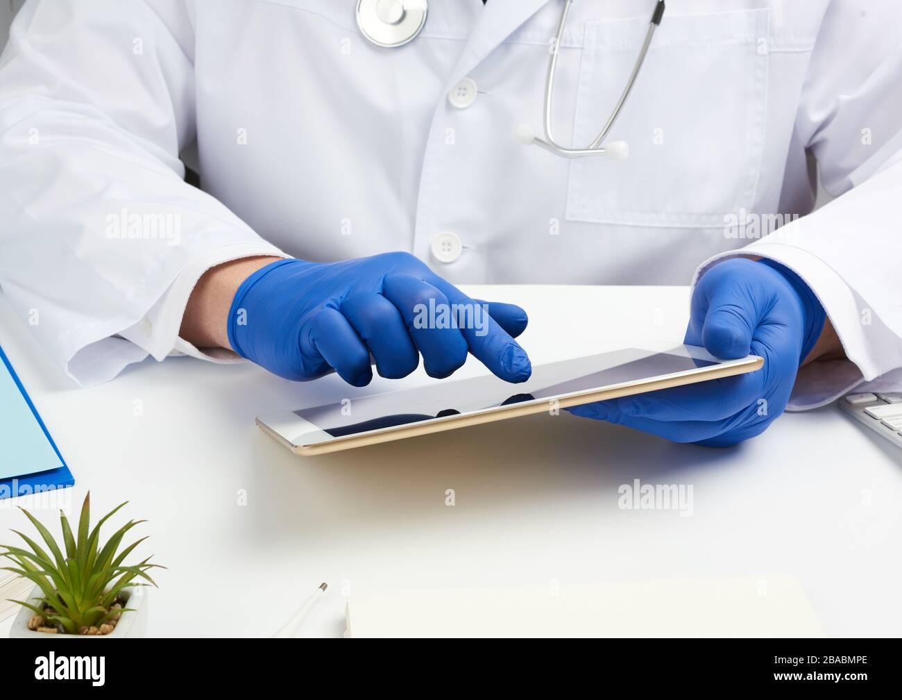 doctor en un abrigo médico blanco se sienta en una mesa y sostiene una tableta electrónica en su mano, toca la pantalla con su mano derecha, el consultorio del doctor, di Foto de stock