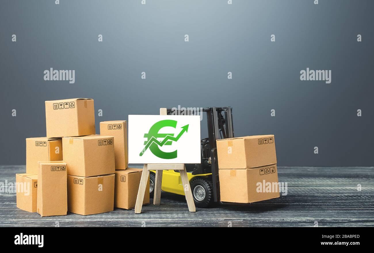 Carretilla elevadora cerca de cajas y caballete con euro verde tasa de crecimiento de tendencia positiva. Aumentar las ventas de las tasas de producción de rade. Crecimiento económico y recuperación. Incrementos de precio Foto de stock