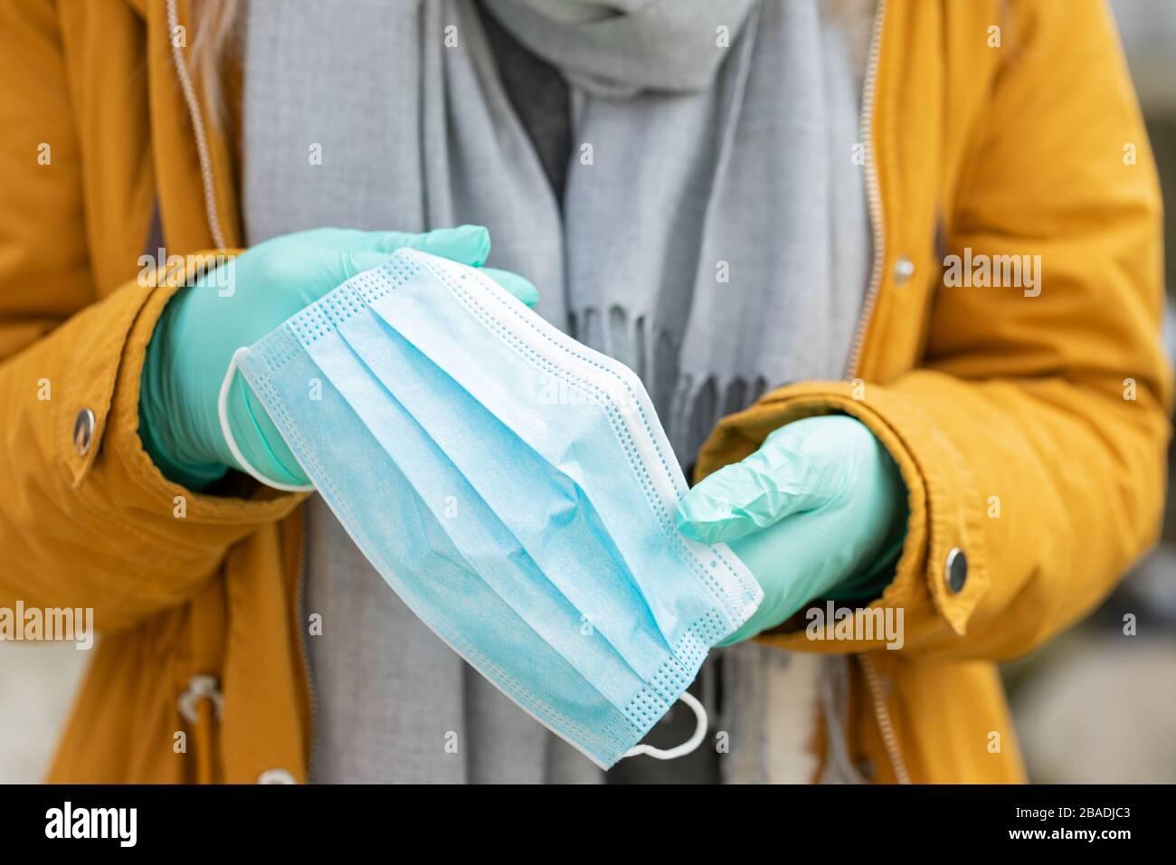 Imagen de cerca de la mujer que sostiene la máscara protectora, usando guantes debido a la pandemia del coronavirus Foto de stock