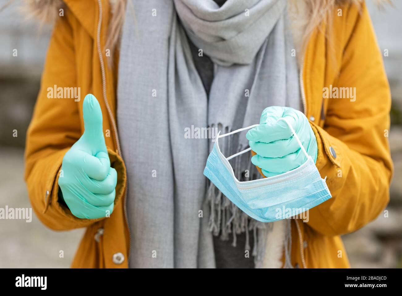 Imagen de cerca de la mujer que sostiene máscara protectora, guantes, mostrando pulgares para arriba - pandemia de coronavirus Foto de stock