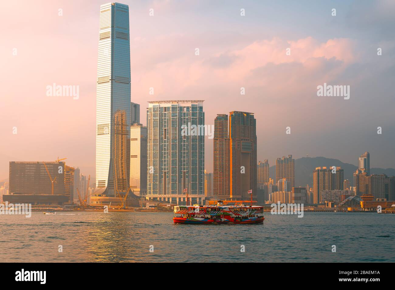 Central, Hong Kong - 1 de marzo de 2020: Ferry estrella y rascacielos con la puesta de sol en el puerto de Victoria Foto de stock