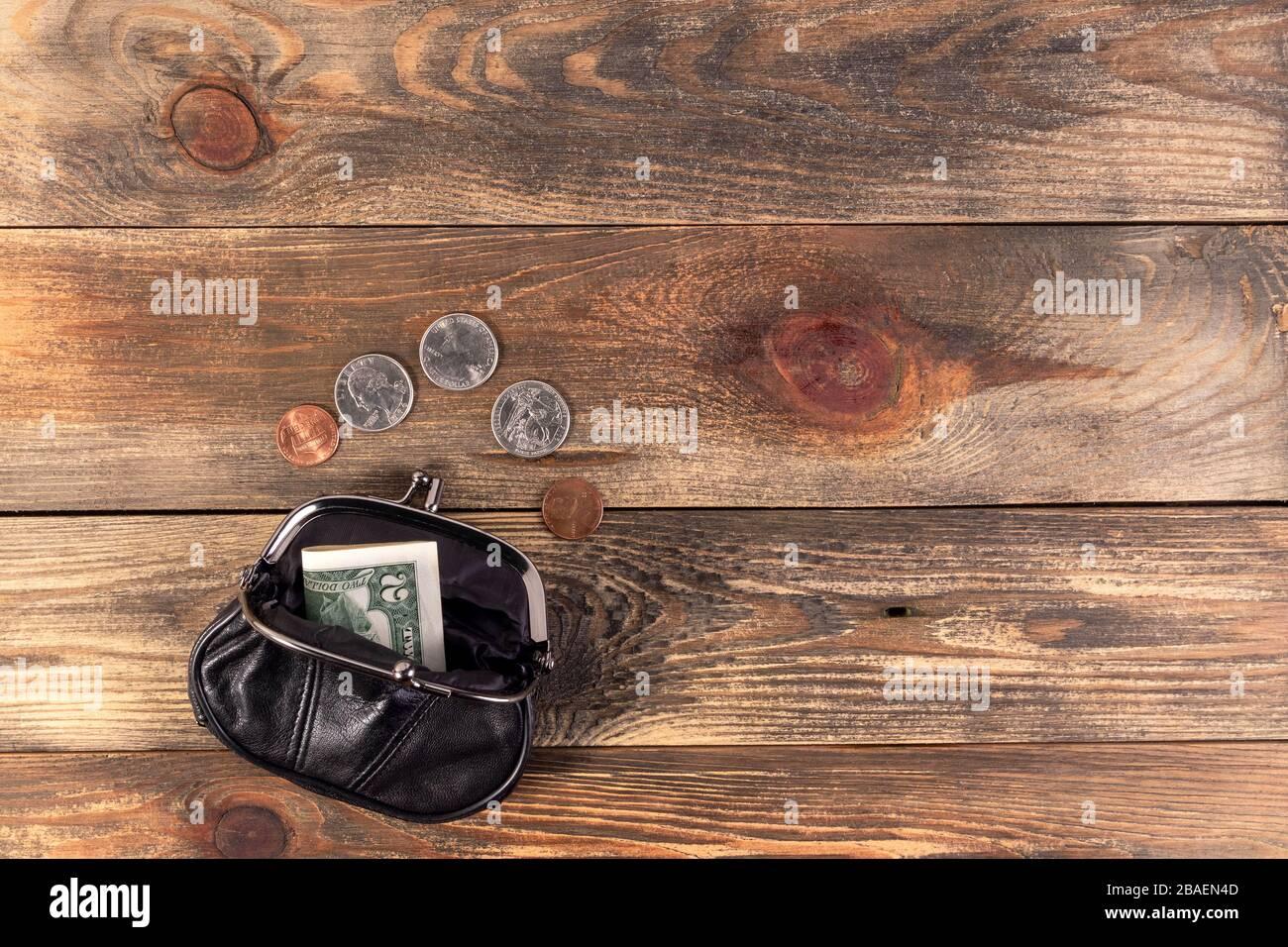 Cartera de bolsillo de cuero negro abierto con monedas de un céntimo, un cuarto de dólar y un billete de 2 dólares cerca. Crisis financiera, pobreza, falta de dinero. Sobre madera b Foto de stock