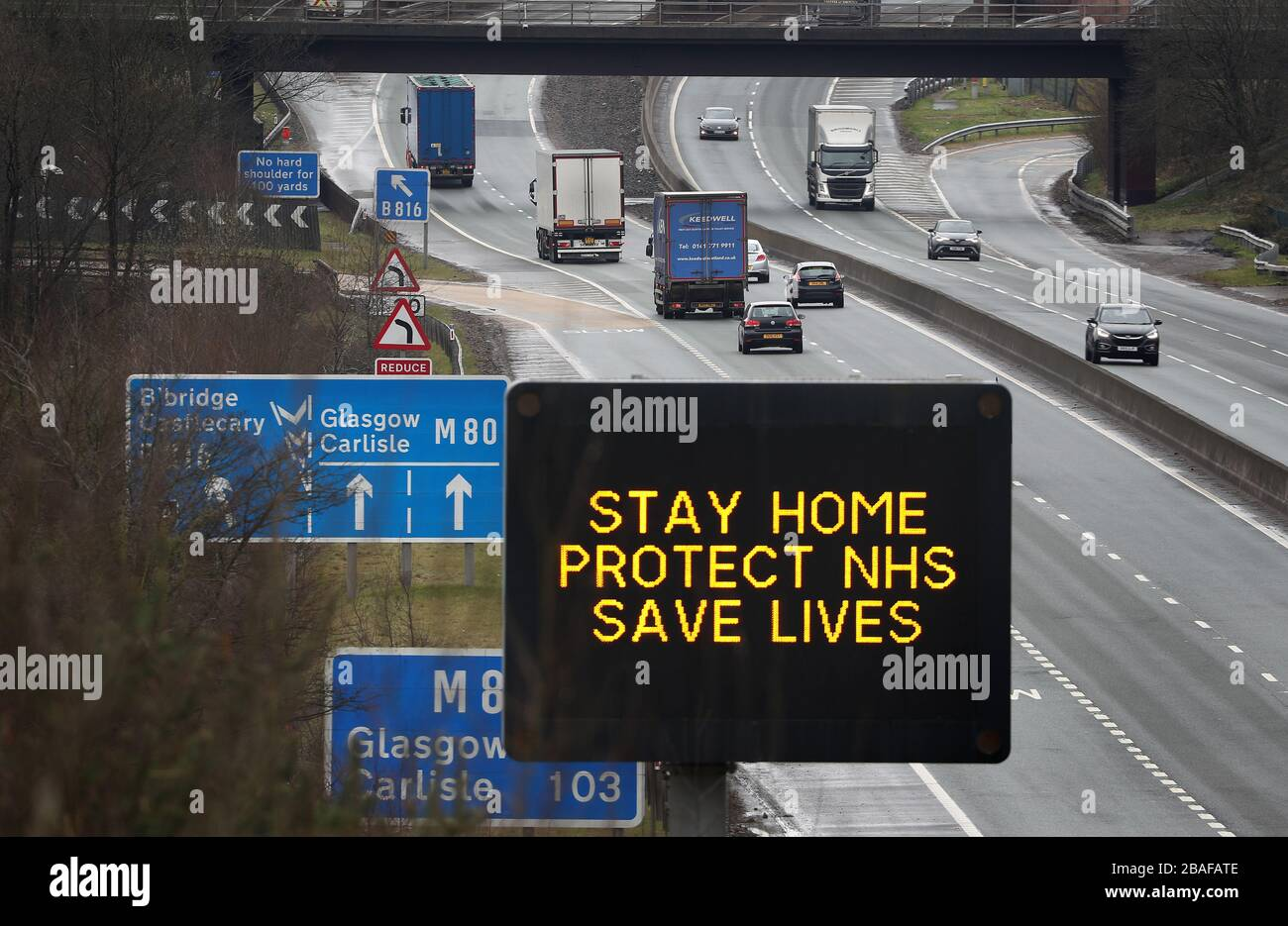 Una señal de carretera que aconseja a los conductores permanecer en casa proteger NHS salva vidas es visible en la M80 cerca de Banknock, ya que el Reino Unido continúa en bloqueo para ayudar a frenar la propagación del coronavirus. Foto de stock