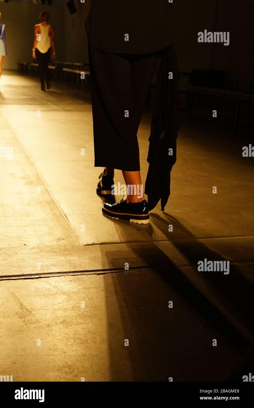 Entre bastidores en la pasarela con zapatos de plataforma negro brillante. Foto de stock