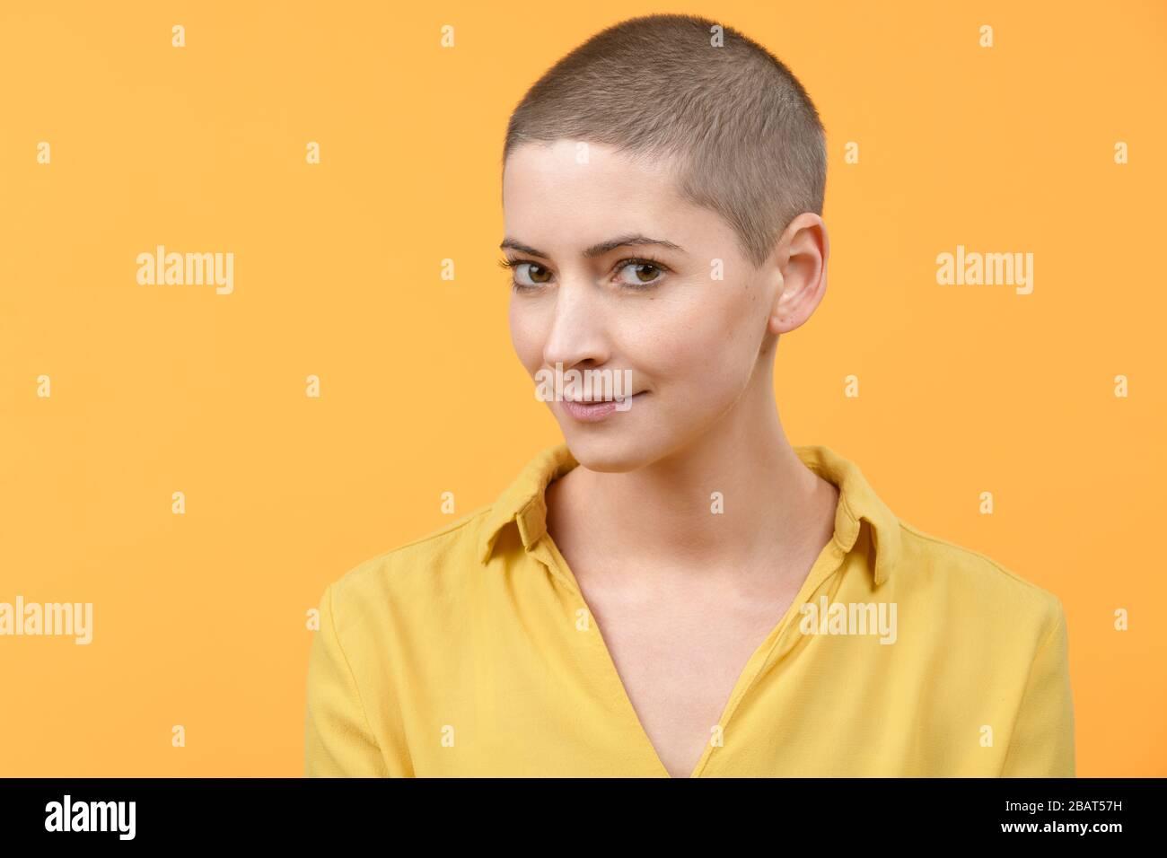 Retrato de estudio de una hermosa mujer caucásica joven con cabeza afeitada sobre fondo amarillo brillante. Retrato de sobreviviente de cáncer. Foto de stock