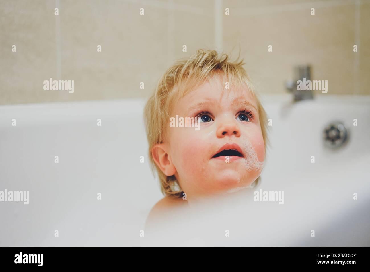 Niño jugando en el baño con burbujas Foto de stock