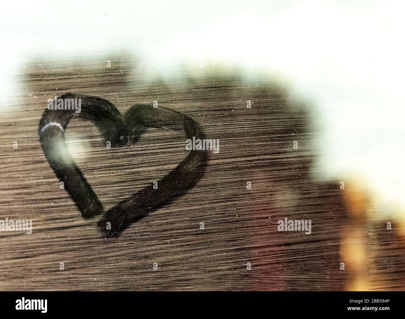 Corazón dibujando en una ventana de cristal mostrando el concepto de la lucha para hacer frente a la depresión durante la cuarentena en el hogar y el distanciamiento social Foto de stock