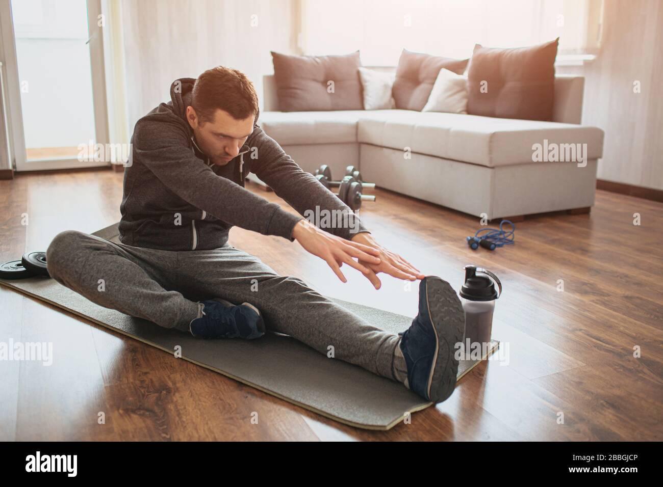 El joven hombre común va a practicar deporte en casa. Freshman o principiante estirando con las manos de remolque a una pierna. Excercising solo en apartamento vacío. Inténtelo a. Foto de stock