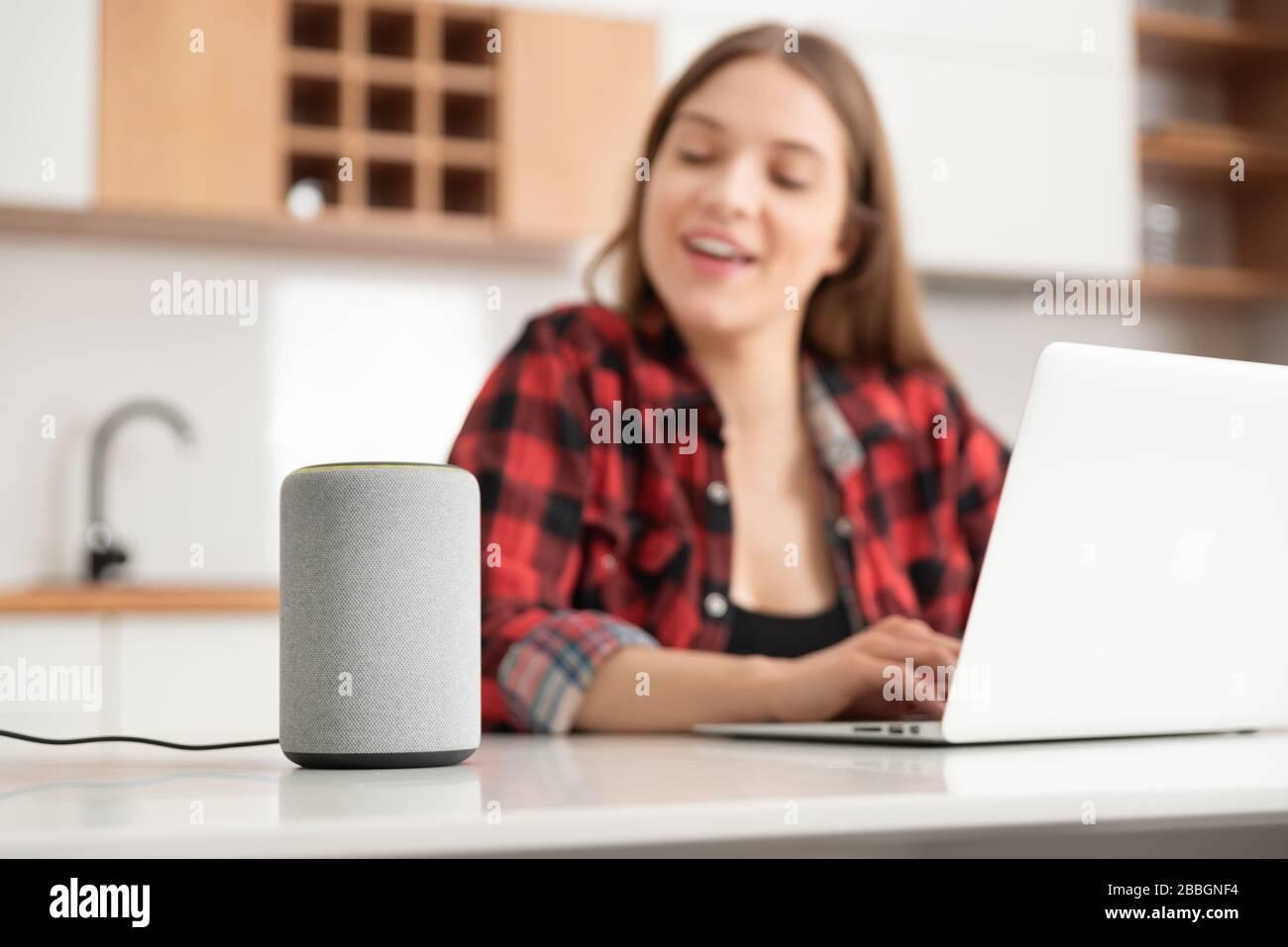 Mujer hablando con un altavoz inteligente. Asistente inteligente en sistema de hogar inteligente. Foto de stock