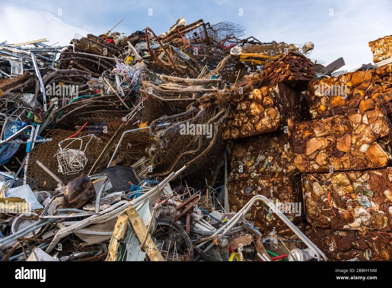 Cubos de latas oxidadas prensadas y apiladas junto a otros desechos en un patio de desechos. Foto de stock
