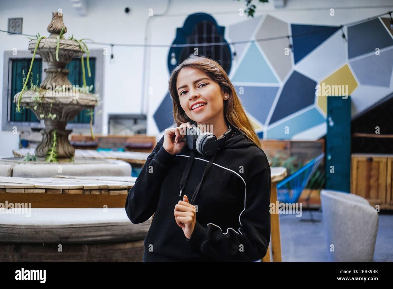 Feliz adolescente latina escuchando música en auriculares en la ciudad de México Foto de stock