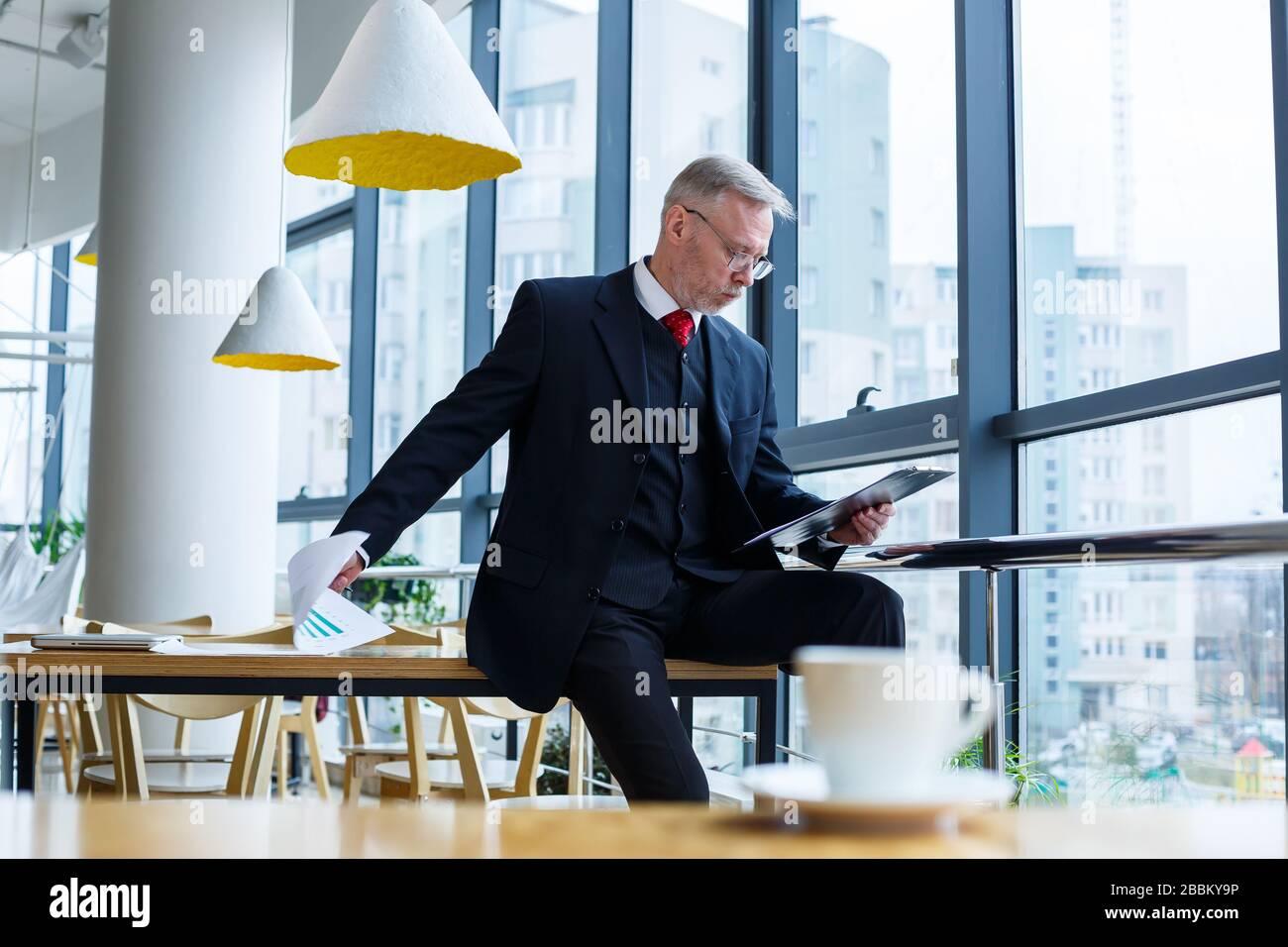 El director general del hombre se inclinó sobre una mesa de madera en su oficina cerca de una ventana grande y observa un plan de desarrollo empresarial exitoso. Foto de stock