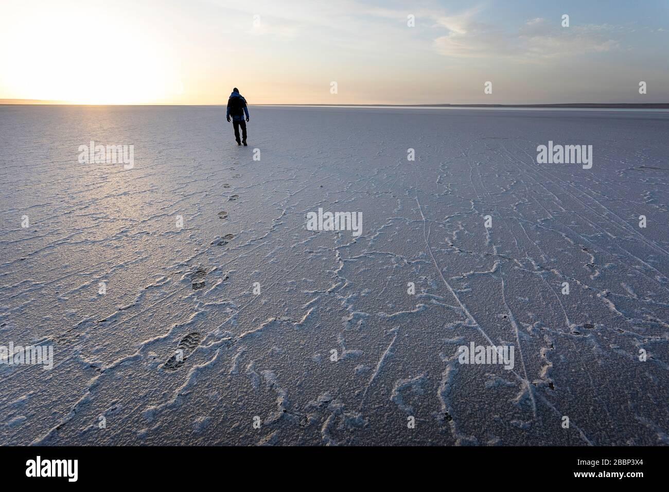 Hombre caminando sobre terreno salado, huellas de pies leaveng en el espectacular paisaje del lago salado de Tuzbair, Aktau, Mangystau, Kazajstán, Foto de stock