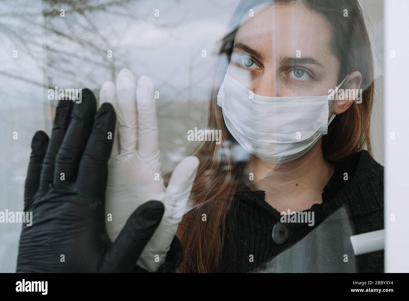 mujer en cuarentena viendo a su frita que vino a visitarla debido a coronavirus covid-19 máscara y guantes en la ventana en casa Foto de stock