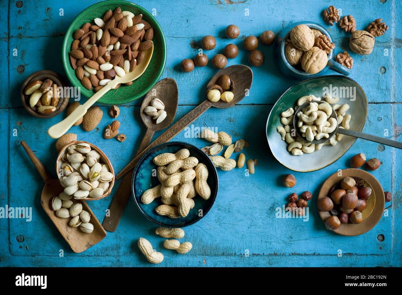 Vista superior de varios frutos secos en cuencos y en cucharas en una mesa rústica azul Foto de stock