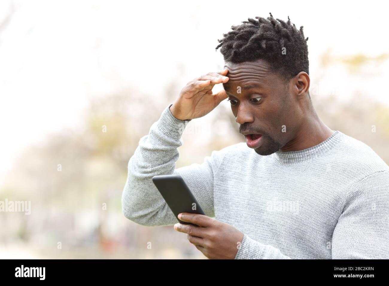 Sorprendido hombre negro comprobando teléfono móvil increíble noticias de pie en un parque Foto de stock