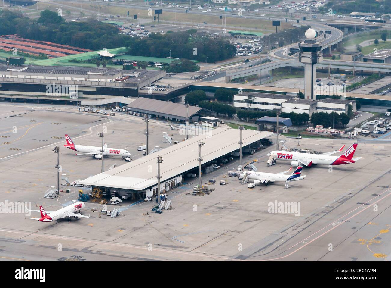 Puesto a distancia estacionó aviones de LATAM (TAM antiguo). Vista aérea de la terminal de pasajeros en el Aeropuerto Internacional Guarulhos de Sao Paulo en Brasil. Torre ATC. Foto de stock