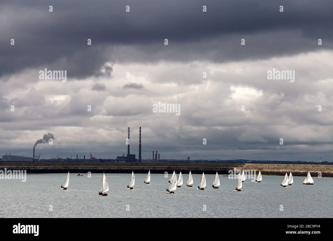 Barcos de vela en el puerto de Dun Laoghaire con Poolbeg Stacks en la distancia Foto de stock