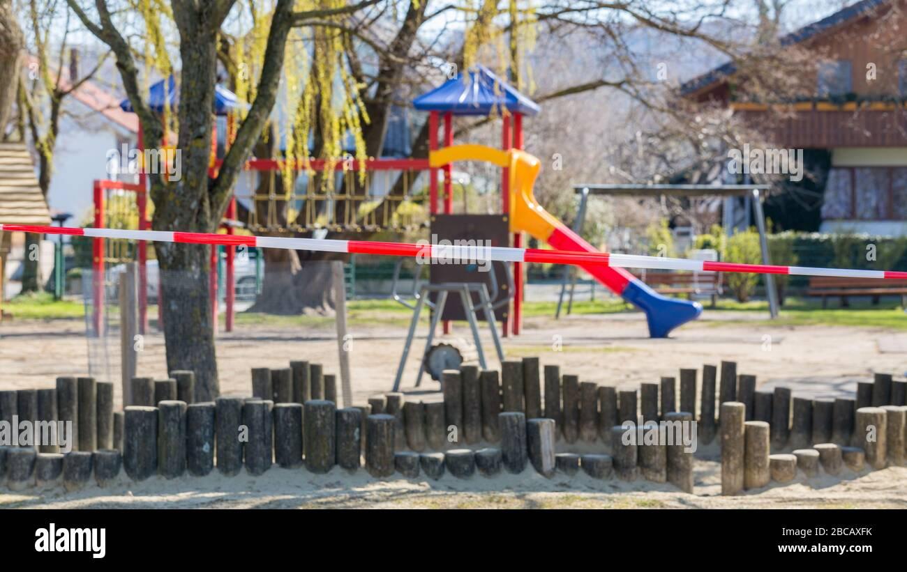 Parque infantil sin niños. Cerrado con cinta de barrera roja - blanca. Prohibido entrar debido a las restricciones de Coronavirus (Covid-19). Foto de stock