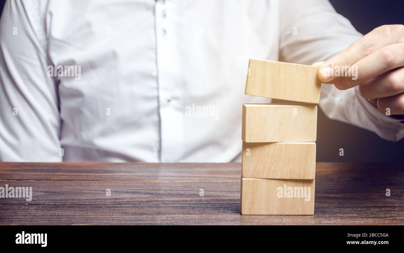 Businessman pone bloques de madera. Gestión de riesgos. Concepto de gestión empresarial. Planificación y estrategia. Establecimiento y logro de metas. Rendimiento. Foto de stock