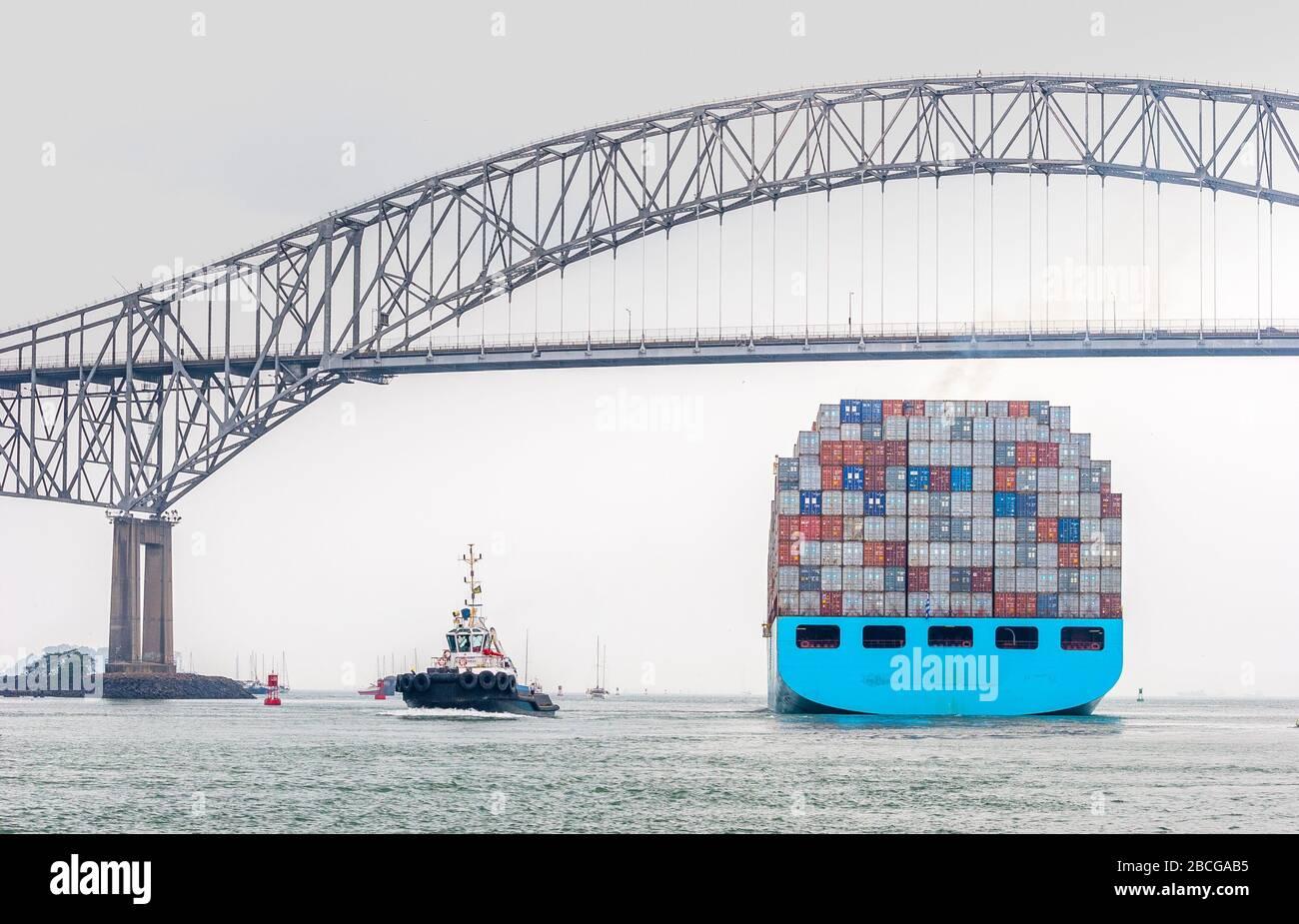 Buque contenedor que sale del Canal de Panamá y pasa por el puente de las Américas, la única vía de conexión entre el norte y el sur de América Foto de stock