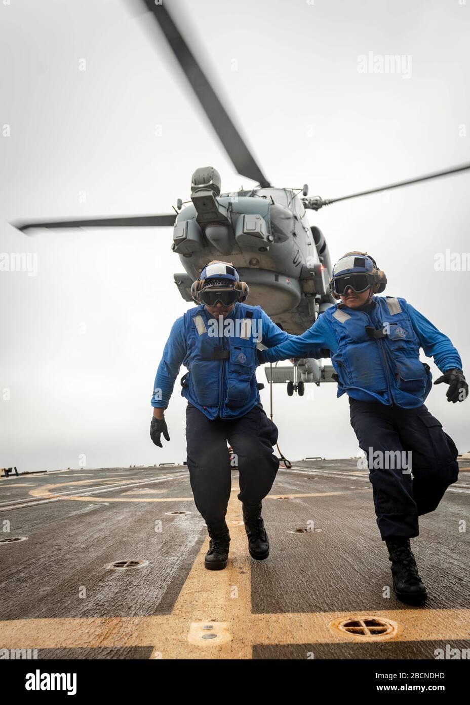 200327-N-WI365-2030 MAR 27, 2020) – Especialista culinario de la Marina de EE.UU. Miquale Claude de tercera clase, izquierda, de Emporia, Virginia, Y Especialista en Logística de 3ª clase Ivan Rojas, de Dallas, corre hacia la línea de la cubierta de vuelo a bordo del destructor de misiles guiados de la clase Arleigh Burke USS McCampbell (DDG 85) durante un entrenamiento de reabastecimiento vertical el 27 de marzo de 2020. McCampbell está llevando a cabo operaciones en la región del Indo-Pacífico, mientras que está asignado al Escuadrón Destroyer (DESRON) 15, el mayor DESRON desplegado hacia adelante de la Marina y la principal fuerza de superficie de la 7a flota de Estados Unidos. (EE.UU Navegación Foto de stock