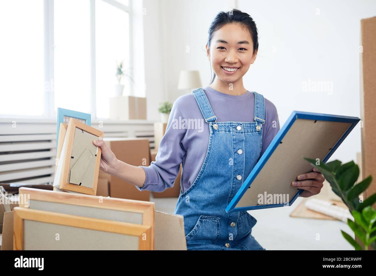 Retrato de una mujer asiática joven embalando cajas y sonriendo en la cámara entusiasmada por moverse a casa nueva o apartamento, copiar espacio Foto de stock