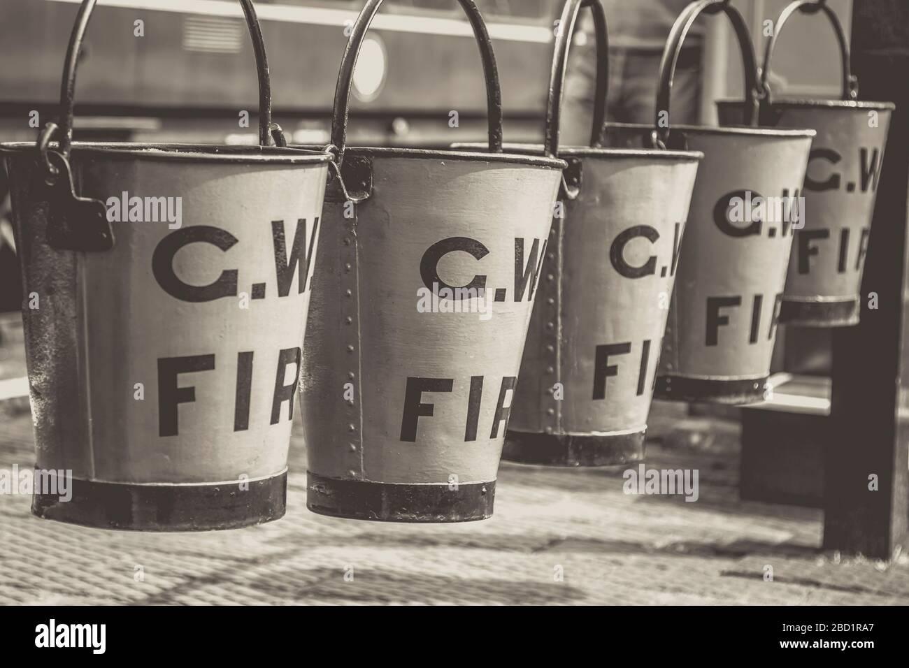 Mono cerca de cubos de fuego vintage colgando en una fila en la plataforma de la estación de tren de época, tren de vapor del valle de Severn. Equipo de lucha contra incendios antiguo. Foto de stock
