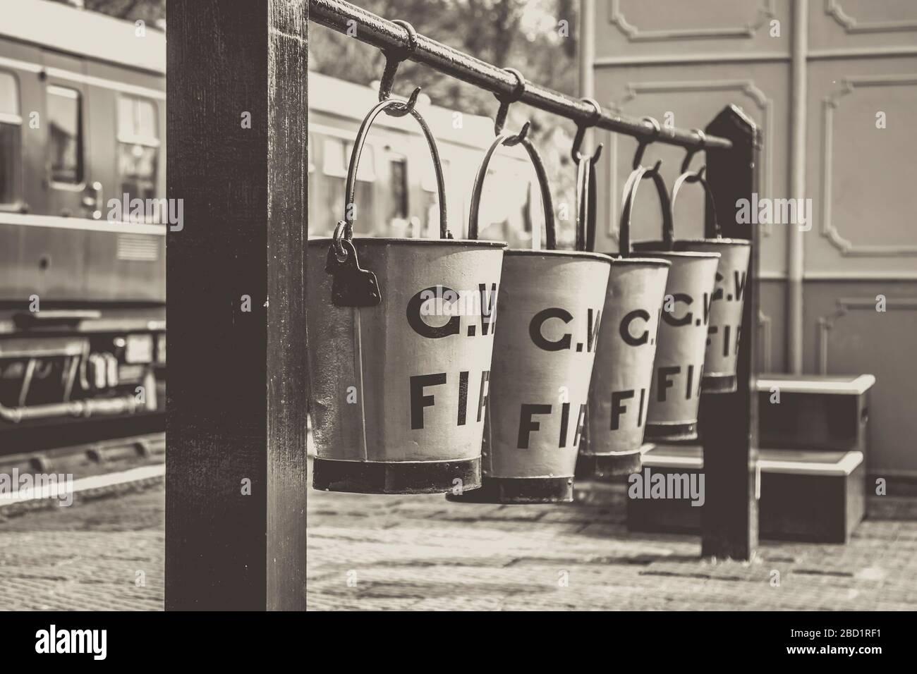 Baldes de fuego negro y blanco añejo colgando en una fila en la plataforma de la estación de tren de época, tren de vapor del valle de Severn. Equipo de lucha contra incendios antiguo. Foto de stock