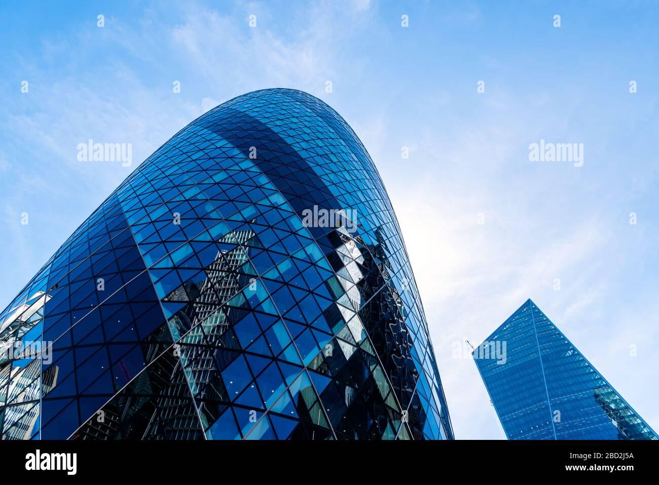 Londres, Reino Unido - 14 de mayo de 2019: Vista de bajo ángulo de los edificios de oficinas en la ciudad de Londres contra el cielo azul. 30 San María Ax o Gherkin Buiding por Norman Fost Foto de stock