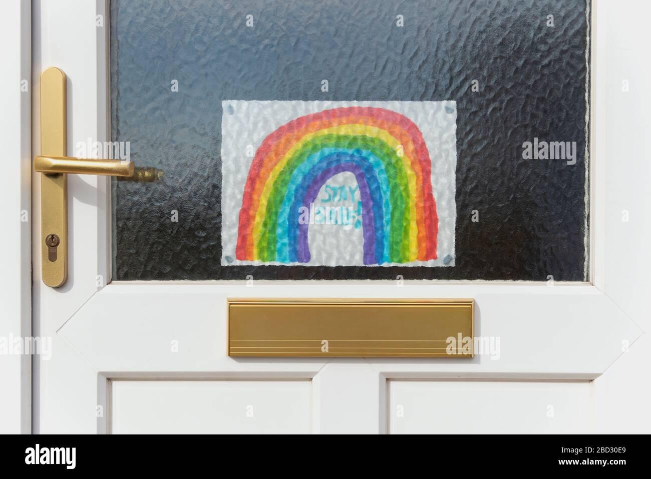 Dibujo de un arco iris pegado a una puerta principal durante la pandemia de Covid-19 de 2020, alentando a la gente a permanecer segura permaneciendo en casa, por Anna Anderson Foto de stock