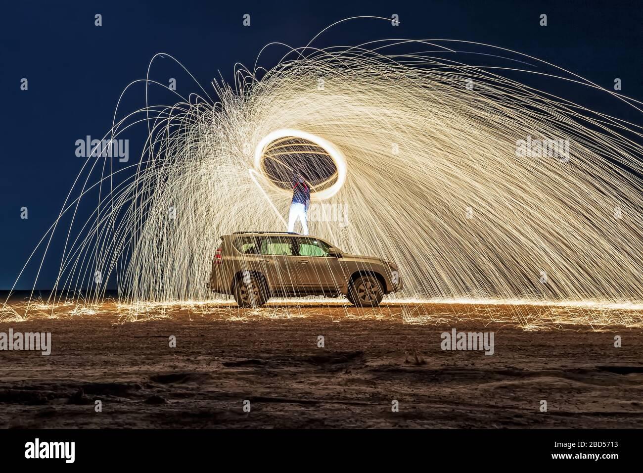 Una lana de acero al fuego por la noche (fotografía nocturna con una velocidad de obturación lenta), con enfoque selectivo. Foto de stock